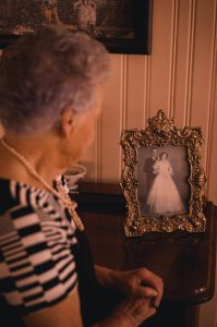 senior citizen looking at wedding photo
